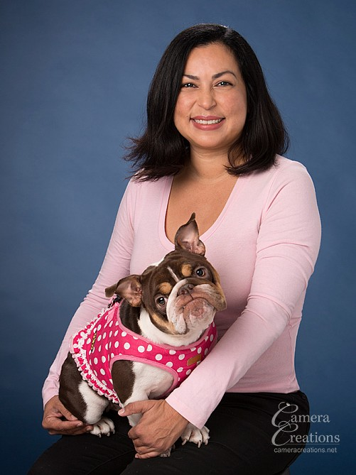 Pet sitter, Elena Araujo, with a dog at her professional headshot session.