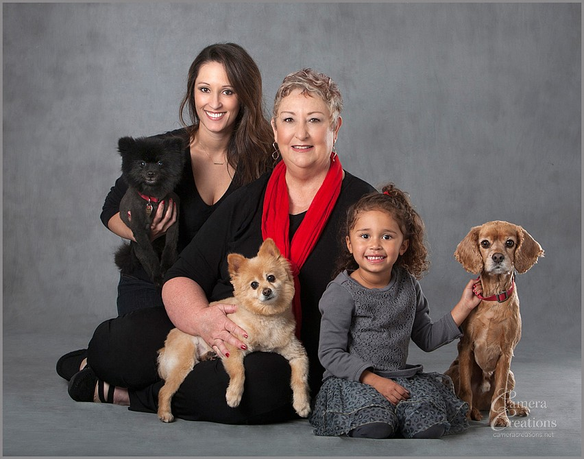 Family portrait photography with three dogs, and three generations of women (grandmother, mom and granddaughter) at Camera Creations LLC studio in Los Angeles. Each generation of ladies have their own are holidng their own dog.