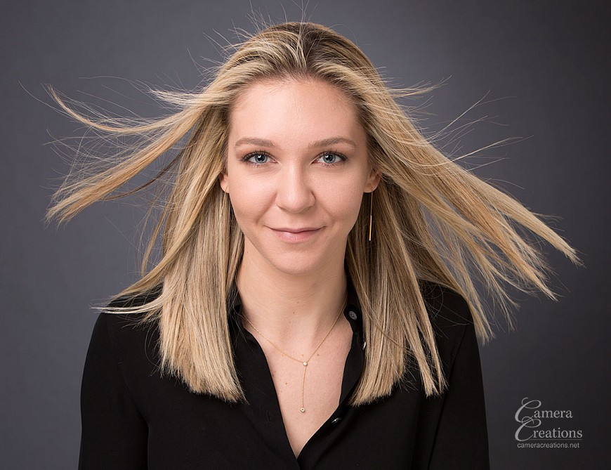 Headshot for a young professional at Camera Creations' portrait studio using a bit of wind for fun.