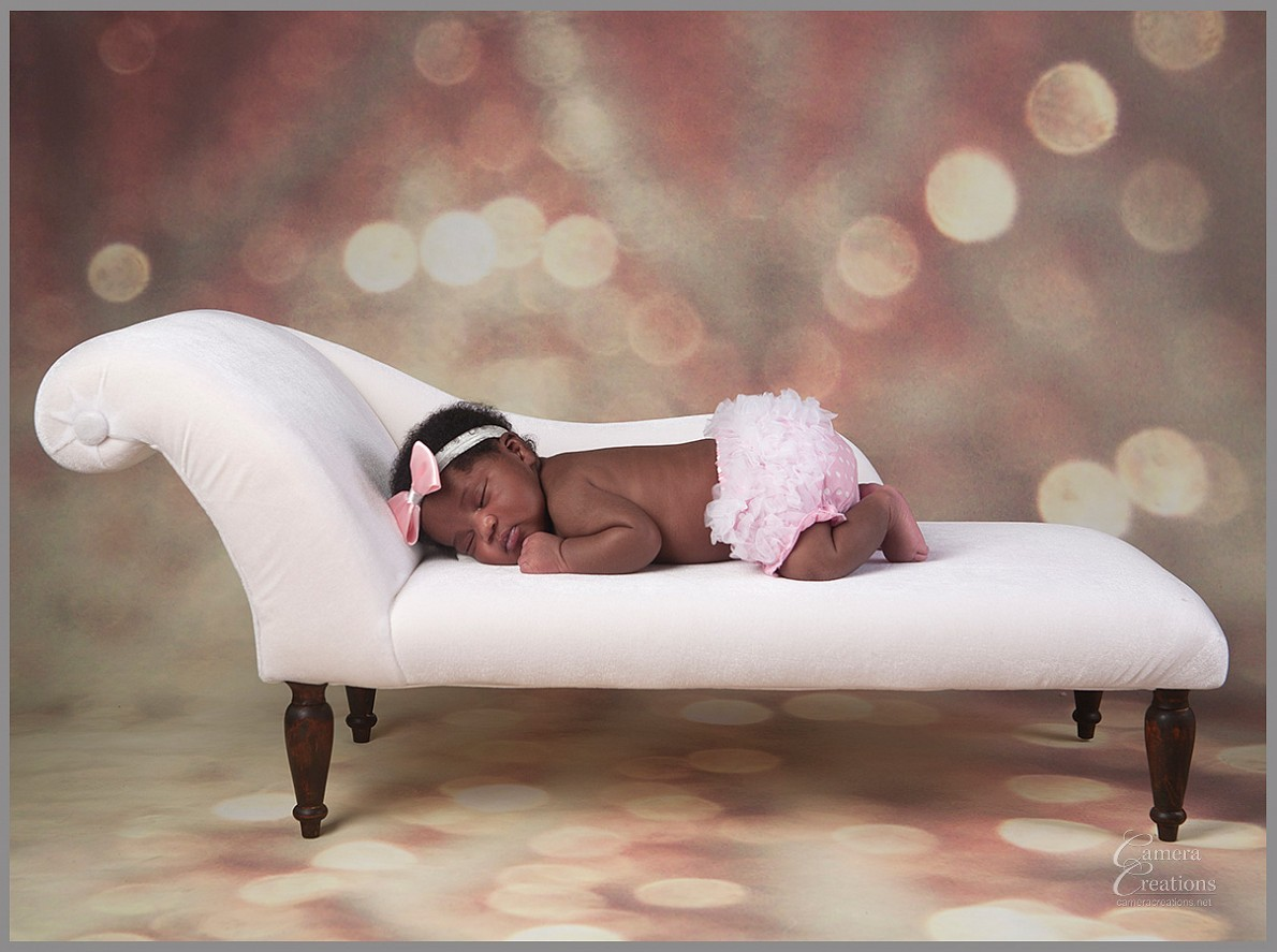 Sleeping newborn baby on divan.